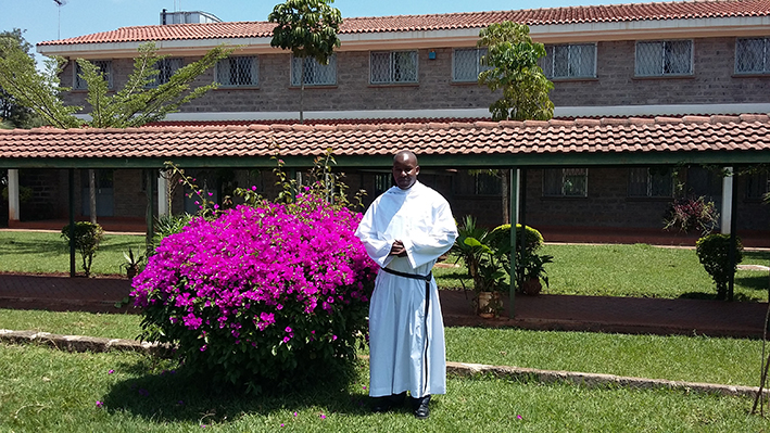 A Kenyan Augustinian with the Priory in the background