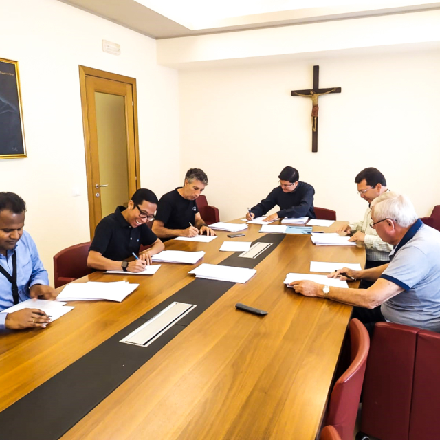 A group of six Augustinians working at a table.