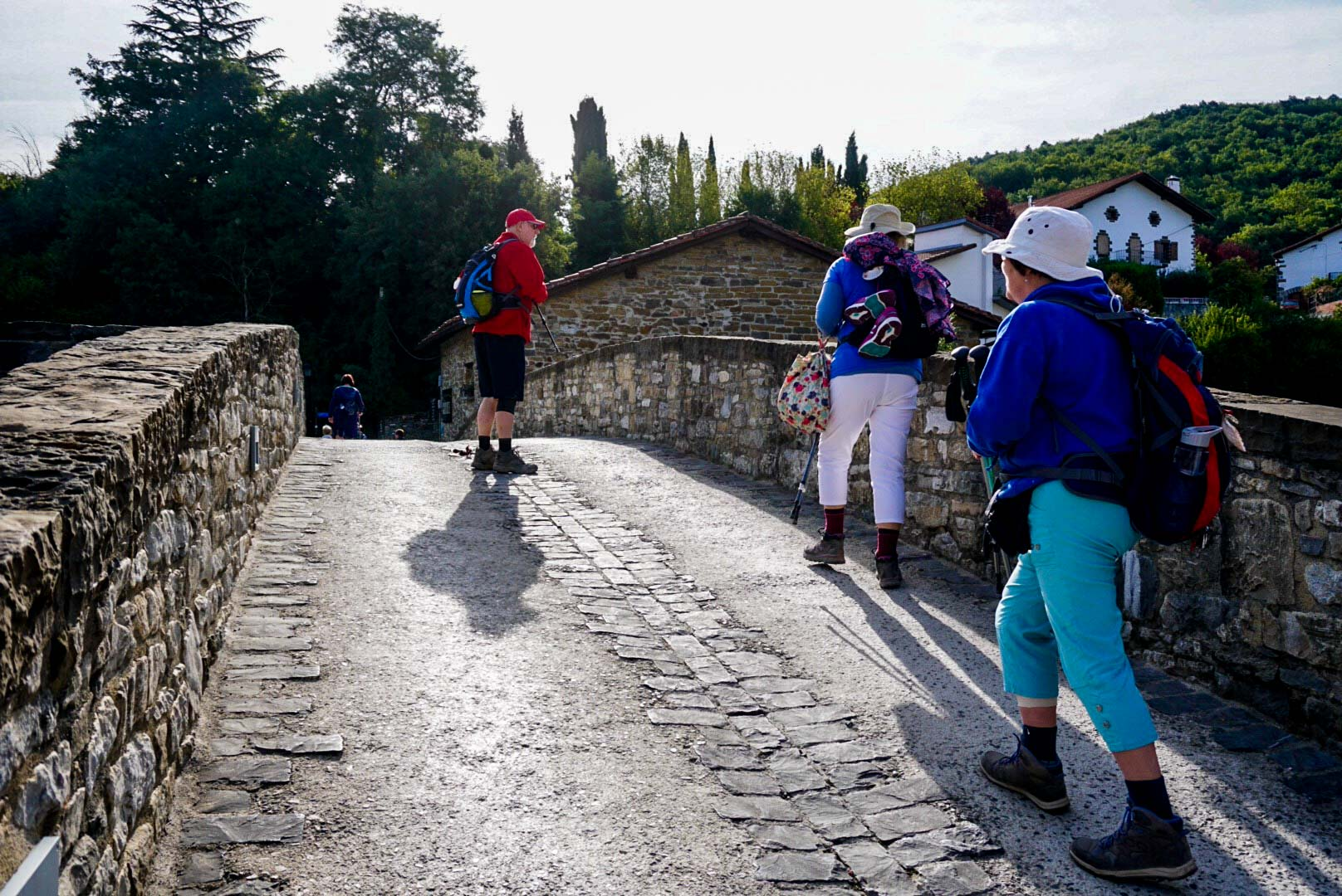 Three people walking over a bridge along the Camino De Santiago.