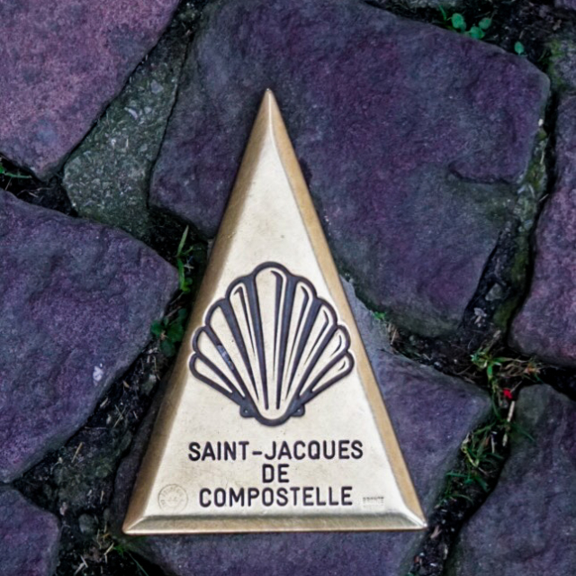 A brass sign post on a pathway marking the route along the Camino De Santiago.