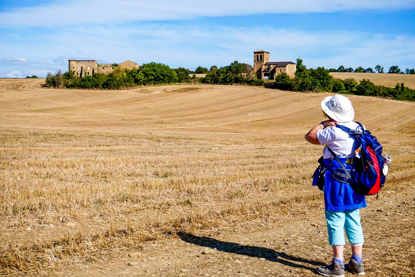 A person standing in a field and enjoying the view of a village on the Camino De Santiago.