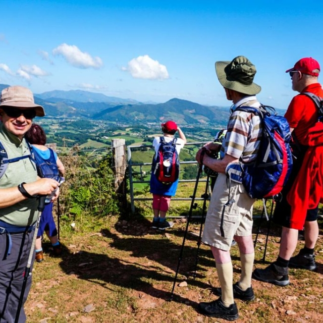 Six people enjoying the view of a valley along the Camino De Santiago.