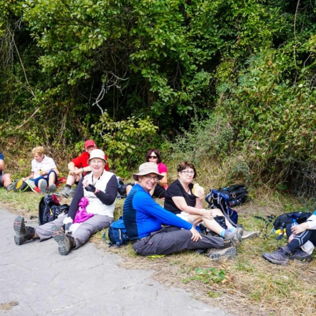 Eight people resting along the path of the Camino de Santiago.