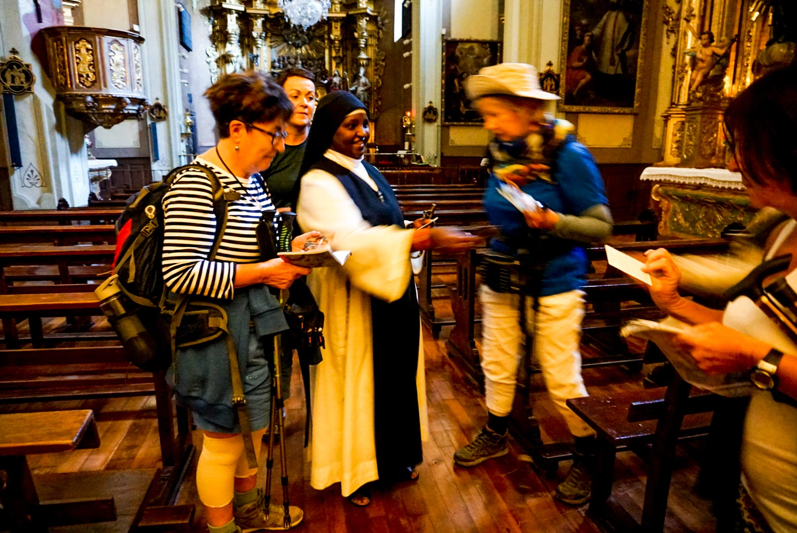 Four people getting their Camino passports stamped by a nuns in a church.