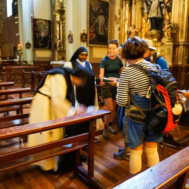 Five people getting their Camino books stamped by two nuns in a church.