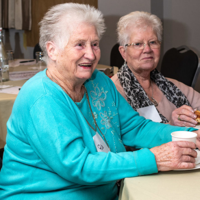 Two women having a cup of tea at a table.