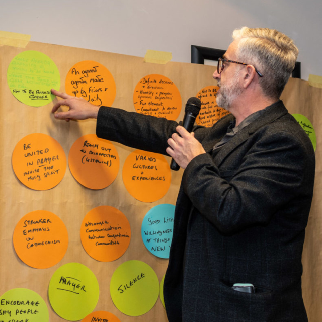A Lay Augustinian speaking into a microphone and sharing ideas from an ideas wall.