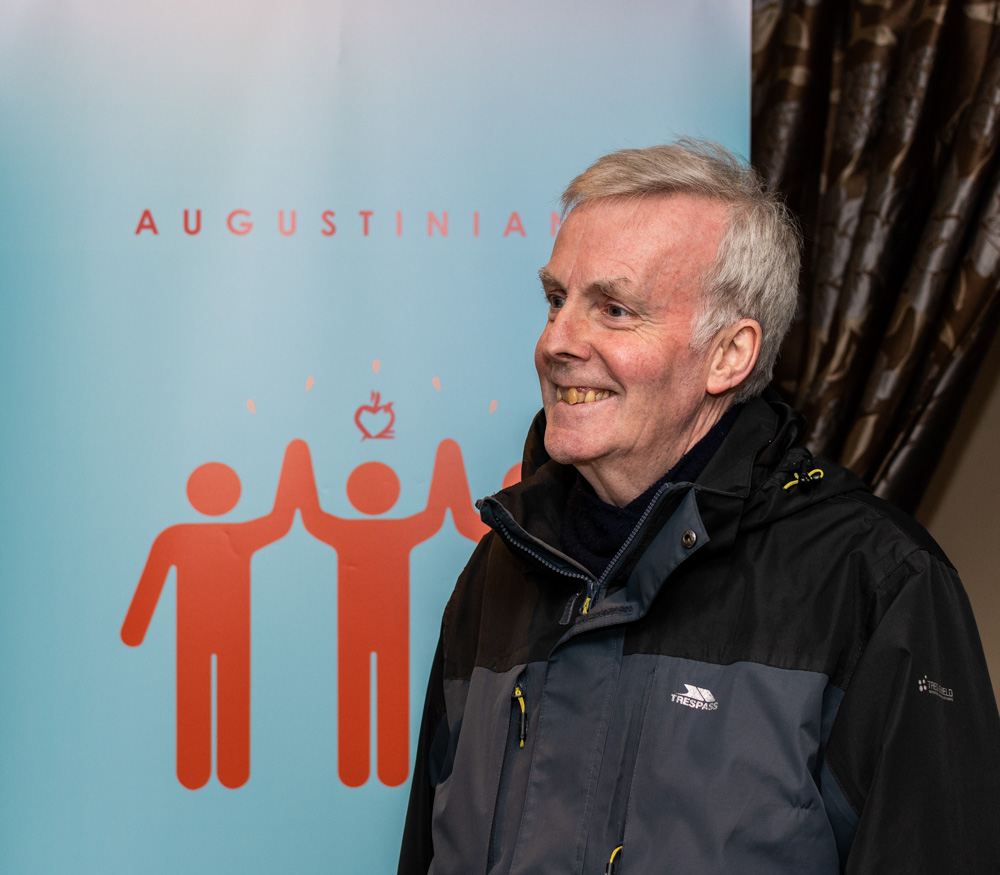 Augustinian standing in front of an Augustinian Poster
