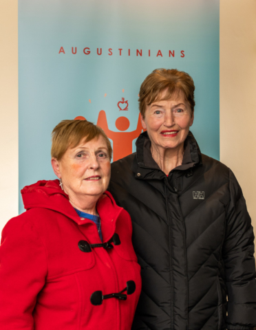 Two Lay Augustinians standing in front of an Augustinian poster at the Augustinian Lay Forum Meeting, Limerick.