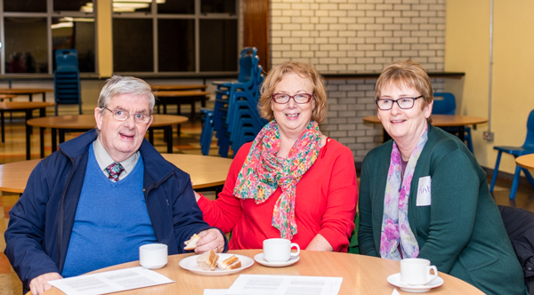 Three people sitting at a table at the Dungarvan Lay Forum Meeting.