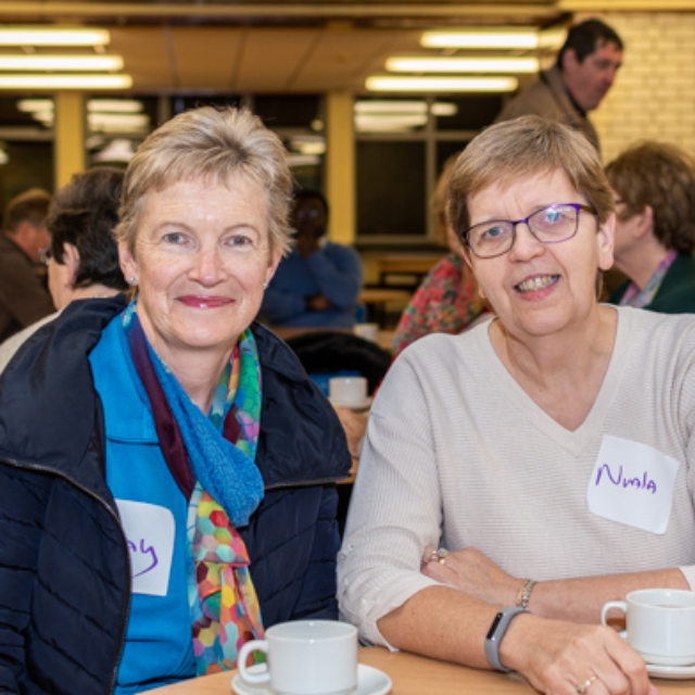Two people smiling at a table at the Dungarvan Augustinian Lay Forum Meeting.