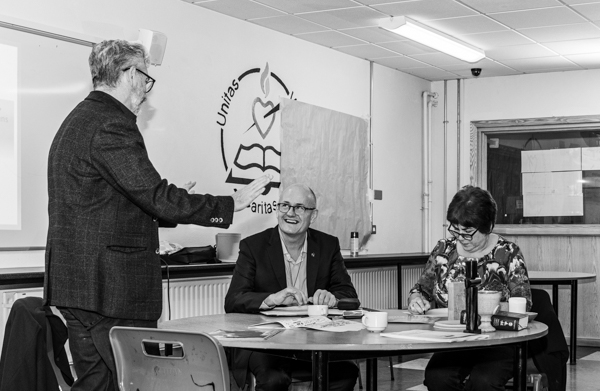 Two people laughing at the Dungarvan Augustinian Lay Forum Meeting, while another person writes at a table..