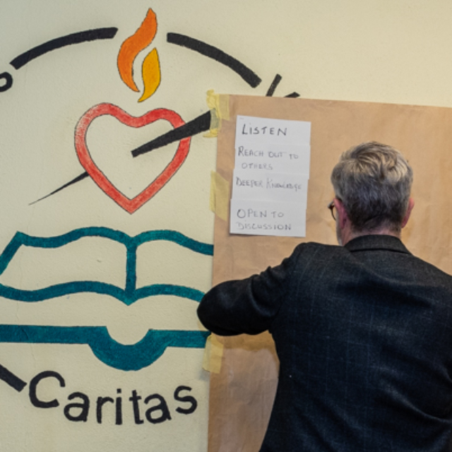 A man posting ideas on a wall Dungarvan Augustinian Lay Forum Meeting.