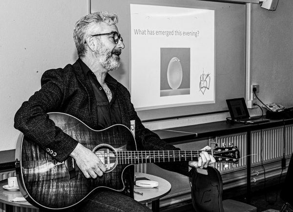 A man playing a guitar at the Dungarvan Augustinian Lay Forum Meeting.