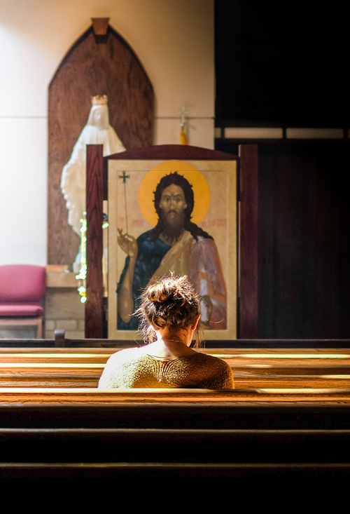 A lady praying in a church.