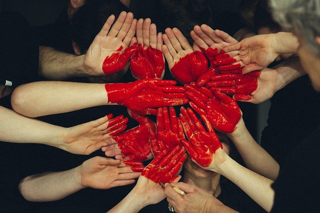 Hands painted red to make a heart.
