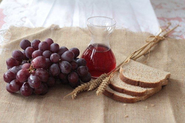 Grapes, Wine and Bread on a table.